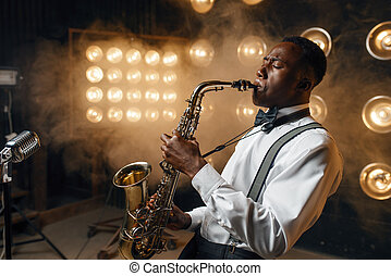 Black jazz performer plays the saxophone on the stage with spotlights. Black jazzman preforming on the scene