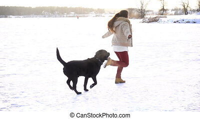 black labrador running with young girl on snow field - black...