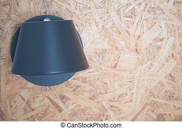 Black lamp on a wooden wall