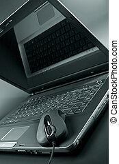 Black laptop and black mouse