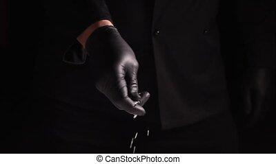 black latex gloved hand sprinkles white coarse salt on black...