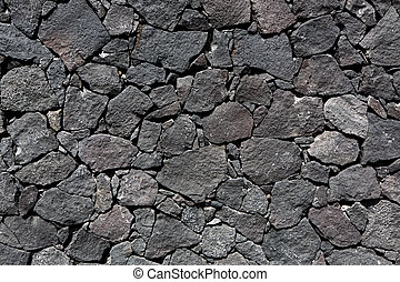 Black lava stone volcanic masonry wall in Canary Islands