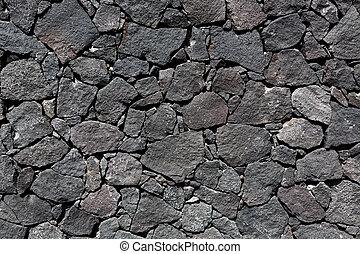 Black lava stone volcanic masonry wall in Canary Islands