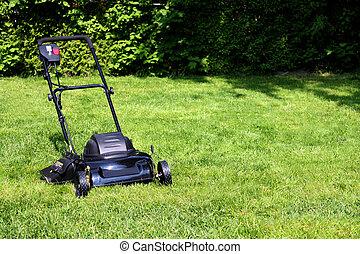 lawnmower - Black lawnmower on freshly cut backyard grass