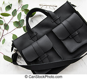 Black leather bag on a marble background
