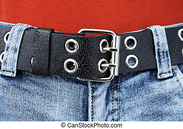Black leather belt with metal buckle and blue jeans.