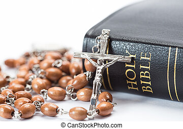 Black leather bound holy bible with rosary beads on white ...