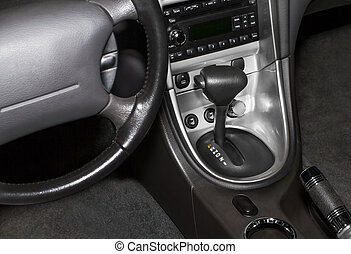 Black leather modern luxury car interior with chrome audio system, gearshift, and climate control.