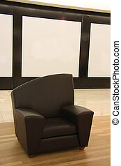 Black leather sofa chair with wooden floor