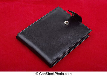 Black leather wallet isolated on the red background. Studio shot.