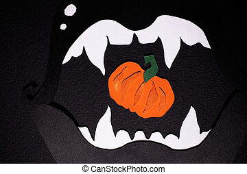 Black lips with white fangs cut out of paper with orange pumpkin inside