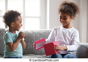 Black little brother presenting gift box for sister