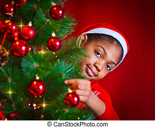 black girl dressed as Santa Claus who decorate the Christmas tree with lights, balls and candles