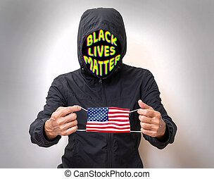 Black lives matter man holding US flag face mask. protester and COVID-19 situation in America