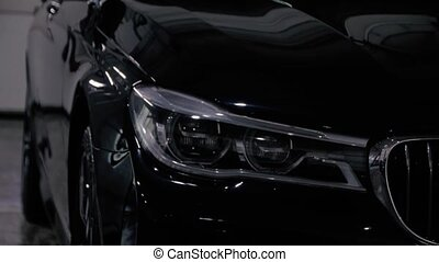 Black luxury car washes with a pressure washer