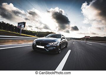 Black luxury sedan driving on the road under dark clouds