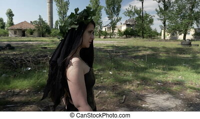Black magic witch in gothic dress walking and calling with...
