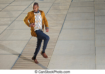 Black male fashion model posing outdoors in casual clothes