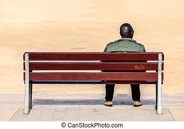 Black male sitting on a bench