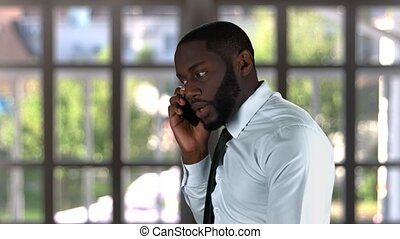 Black male talking on phone.