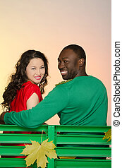 Black man and asian woman on bench in autumn