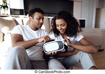 Black man and woman are sitting on the couch. A man and a woman hold a helmet of vr in their hands and dispose of it.