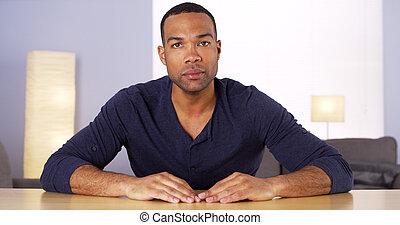 Black man at table looking to camera