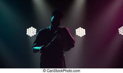 Black man bangs on talking African yuka drum and dances to music against backdrop of bright spotlights and smoke. Silhouette of an African American musician in ethnic clothes. Musical instruments of world culture sound.