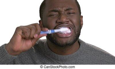 Black man brushing teeth. Process of cleaning teeth by dark...