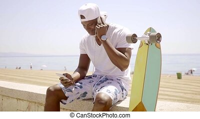 Black man checking his phone while seated on wall