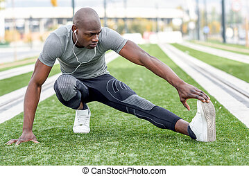 Black man doing stretching before running in urban background