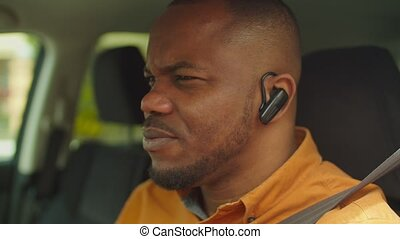 Lifestyle portrait of successful confident african american male entrepreneur driving car, talking using hands-free device in the city. Positive black man driver calling wireless headset in car.