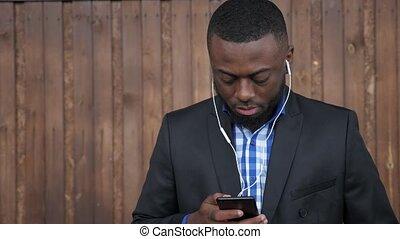 Black man in earphones is browsing mobile phone on dark wood...