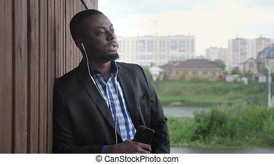Black man in earphones is listening music on phone at city...