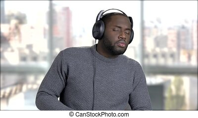 Black man in headphones is dancing.