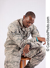Black man in military uniform, looking thoughtful