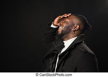 Black man in profile laughing with his hand on his face.