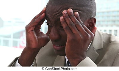 Black man in suit massaging his forehead while sitting in...