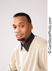 Black man in sweater and bow tie looking at the camera with ...