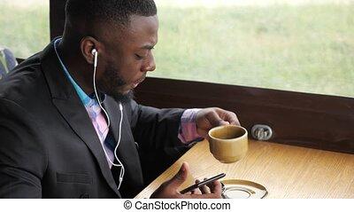 Black man is listening music in earphones browsing...