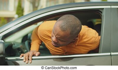 Worried handsome african male driver looking at front tyre and car body from open car window during road trip in the city. Black man checking damaged vehicle during driving in traffic jam.