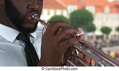 Black man playing trumpet. Musician on street background.
