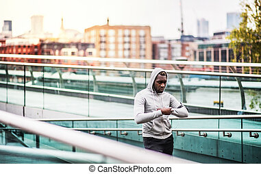 Black man runner resting on the bridge in a city, checking...