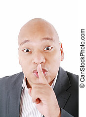 Black man showing silence gesture with finger on his lips. All on white background