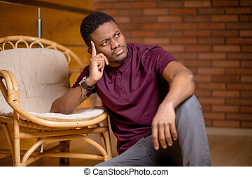black man sitting on the floor and looking at camera