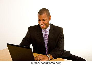 Black Man Smiling Working on Laptop