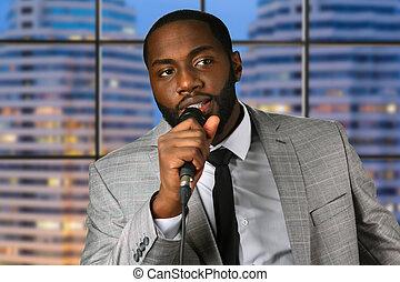 Black man speaks into microphone.