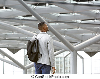 Black man standing alone in airport with bag