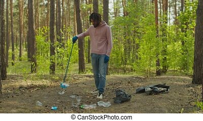 Environmentally friendly stylish african american male volunteer in protective gloves with garden tool picking up litter during spring cleaning in woodland, caring for nature and ecology.