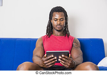 Black man watching movie on tablet PC